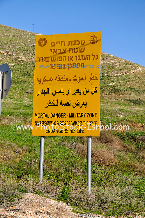 Israel, Golan Heights. The Syrian Israeli border fence a yellow warning sign as seen from the Israeli side