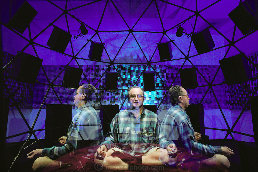 New Age meditation technology. John-David, founder of the John-David Learning Center, inside his Brain/Mind Intensive Dome. The client sits inside the geodesic dome, and is slowly rotated. A 'self- improvement' tape is played through the speakers in the dome, along with other sounds that are said to 'tune-up' the brain. Claimed benefits of long-term use of the equipment include improvements to memory and decision-making abilities and an increase in creativity. The equipment is also claimed to be effective in treating alcohol or drug dependency. The John- David Learning Center is in Carlsbad, California. MODEL RELEASED [1988] Triple exposure.