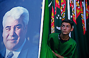 Ashgabat, Turkmenistan, October 1997..A spectator at Independence Day celebrations with a portrait of President Saparmurat Niyazov..Poverty-stricken, but rich in oil and gas resources, this Central Asian former Soviet republic is ruled by the autocratic President Saparmurat Niyazov, or Turkmenbashi as he has renamed himself...............