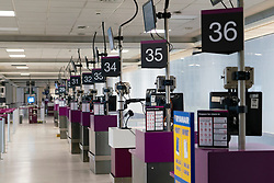 Edinburgh, Scotland, UK. 27 March, 2020. Interior views of a deserted Edinburgh Airport during the coronavirus pandemic. With very few flights during the current Covid-19 crisis passengers are scarce in the terminal building. Row of empty check-in counters. Iain Masterton/Alamy Live News