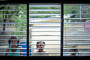 Three girls look from outside of the school window in Azua<br /> <br /> Images for editorial, news usages and creative industry. Spanish born photographer based in Punta Cana, Dominican Republic. Editorial and Commercial Photographer based in Valencia, Spain |Portraits, Hospitality, News, Sports, Media Coverage for Events