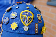 Leeds United fan with baseball cap decorated with badges during the EFL Sky Bet Championship match between Burton Albion and Leeds United at the Pirelli Stadium, Burton upon Trent, England on 22 April 2017. Photo by Richard Holmes.