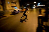 Cuban boy skateboarding at night time under streetlights.