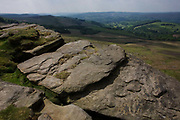 From the top of an escarpment, we see a wide landscape of Gritstone geology on Long Causeway cliffs, Peak District National Park, Derbyshire. This is the top of Stanage Edge gritstone cliffs. Beyond is a beautiful panorama of the Peak District National Park in England. Stanage Edge is the largest of the gritstone edges that overlook Hathersage in Derbyshire. Stanage Edge at approximately 4 miles in length and 458m at its highest point is the largest of the gritstone cliffs that overlook Hathersage, Derbyshire. The area is one of the most popular locations in the Peak District National Park for climbing and walking with hundreds of rock climbing routes to challenge all ranges of ability. Walkers are drawn to the area to enjoy the varied moorland scenery with stunning views across the surrounding countryside.