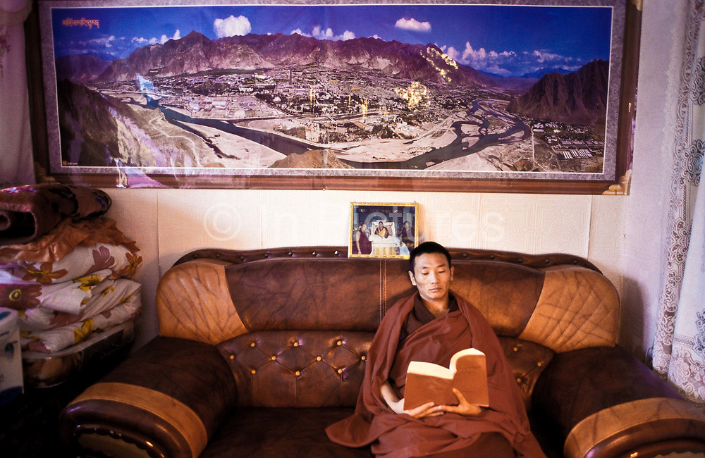 Tibetan buddhist monk Dongyu, reading the Buddha's teachings in his small but well equiped and furnished living space  comprising of a living room / bedroom and a small wood fired kitchen, within the  300 years old walls of Atsog Monastery, Xinghai County, Qinghai Province, China.