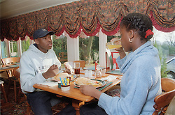 Teenage boy and girl eating lunch together in restaurant,