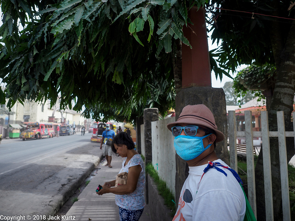 30 JANUARY 2018 - GUINOBATAN, ALBAY, PHILIPPINES: People on the street in Guinobatan during an ash fall. Mayon volcano continued to erupt but not as dramatically as it did last week. The small eruptions are still sending ash clouds over communities west of the volcano and the government is encouraging people to stay indoors, wear face masks and avoid strenuous activities when ash is falling.     PHOTO BY JACK KURTZ