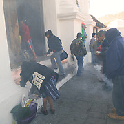 The main church of Chichicastengo, known as Santo Tomas Church, serves as both a K'iche' Maya and Catholic church. In this shot, Maya burn incense and copal resin to create smoke. Chichicastenango is an indigenous Maya town in the Guatemalan highlands about 90 miles northwest of Guatemala City and at an elevation of nearly 6,500 feet. It is most famous for its markets on Sundays and Thursdays.