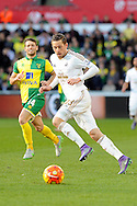 Swansea City's Gylfi Sigurdsson plays a pass watched by Norwich's Wes Hoolahan. Barclays Premier league match, Swansea city v Norwich city at the Liberty Stadium in Swansea, South Wales on Saturday 5th March 2016.<br /> pic by  Carl Robertson, Andrew Orchard sports photography.