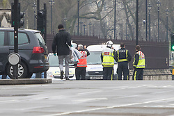 Scotland Yard, London, March 23rd 2017. A man in civilian clothes carries what appear to be evidence bags in the aftermath of Tuesday's terrorist attack on Westminster Bridge and in the grounds of Parliament, in which four people and their attacker were killed with over 40 injured.