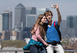 © Licensed to London News Pictures. 05/05/2016. London, UK. A couple in Greenwich Park take a selfie in sight of Canary Wharf. London is expecting 20 degrees of spring sunshine today.  Photo credit: Peter Macdiarmid/LNP