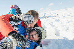 Family tussle in snow, smiling, Bavaria, Germany