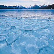 sun sets on snow capped mountains in glacier national park, lake mcdonald, ice covered lake