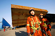 Workers Guo Xianwang (left) and Wang Jiaxiang (right) by the 3AW section of the OBG of Self-Anchored Suspension (SAS) bridge outside the workshops of Shanghai Zhenhua Port Machinery Co. Ltd. (ZPMC), on Changxing Island, Shanghai, on January 12, 2009. The San Francisco–Oakland Bay Bridge (USA), damaged in the 1989 earthquake, is currently being replaced. The new bridge will open by 2012, at an estimated cost of $6.3 billion. What is little known is that its steel parts are being produced near Shanghai, China, and then shipped to the USA, making it the first subcontracted bridge in History. Photo by Lucas Schifres/Pictobank