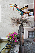 """Public art: a bird on nest holds a fish in Pontresina, Upper Engadine, Graubünden (Grisons) canton, Switzerland, the Alps, Europe. The Swiss valley of Engadine translates as the """"garden of the En (or Inn) River"""" (Engadin in German, Engiadina in Romansh, Engadina in Italian)."""