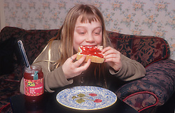 Young girl eating bread and jam,