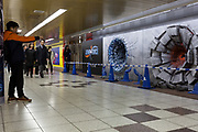 A man takes a photo of one of three craters in a wall advertising the Jump Force video game for Play Station, X-box and Window PC in Shinjuku Station, Tokyo, Japan. Friday February 22nd 2019. Jump Force  game brings together all the most popular characters from the Shonan Jump manga comics.and was released on February 15th. The punch wall represents the effect of a power punch from characters Son Goku of Dragonball, Naruto and Luffy from One Piece and runs to February 24th