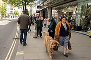 Woman with her dog out and about in the shopping district of Oxford Street, some wearing face masks and others not on 26th May 2021 in London, United Kingdom. As the coronavirus lockdown continues its process of easing restrictions, more and more people are coming to the West End as more retail businesses open.