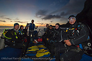 Crew and customers from the Galapagos Sky prepare to scuba dive at night in a protected cove in Wolf Island, Galapagos Islands, Ecuador