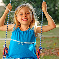 Gleeful girl swings in her backyard in summertime.