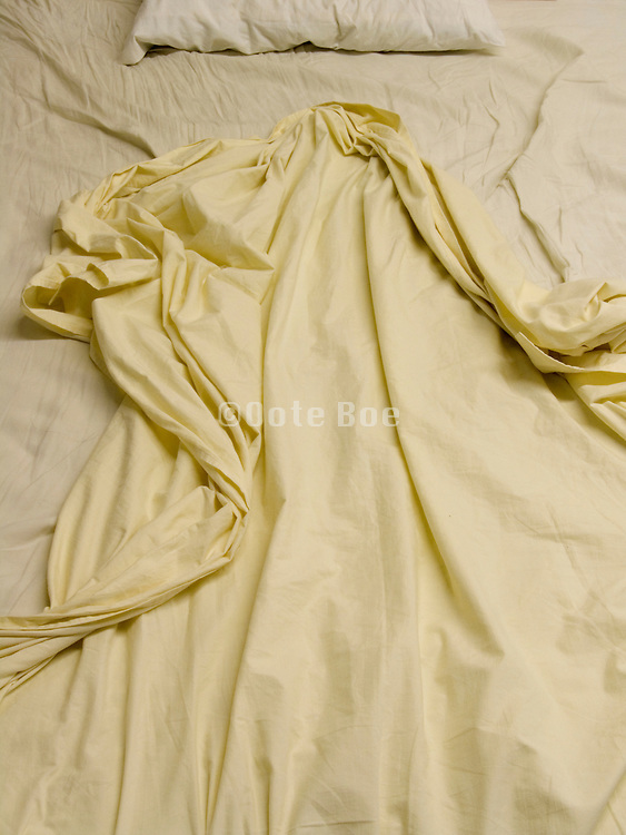 close up of bed with rumpled sheets
