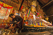 China, Tibet, Gyantse. Pelgor Chode monastery. monk adjusting butter lamps in front of the main deity.