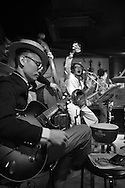 """Tokyo, Japan:  This is """"Tokyo Kan Kan Rhythm"""", a house band that plays 1920s to 1940s style ragtime, dixieland jazz, blues and tin-pan alley songs at Music Bar RPM. This bar is located in the hip and trendy Tokyo neighborhood of Shimokitazawa. The director of this band is Keita Sugiyama, the lead singer, banjo/guitar/ukulele player. He is seen in the white pinstripe suit and straw hat (center), performing on his birthday. Sugiyama is also the manager of Music Bar RPM, a cool live music venue with red walls and regular concerts. The Shimokitazawa neighborhood of Tokyo is known for it's tiny bars, pubs, cafes, theaters, galleries, coffee houses and live music venues. Dec. 10, 2014. Photo by Torin Boyd.<br /> <br /> Address:<br /> <br /> Sloppy Joe's<br /> 2-19-17 Kitazawa, Southern Ishii Bldg. 4F<br /> Setagaya-ku, Tokyo 155-0031 <br /> Tel: 03-3424-0424<br /> Nearest station: Shimokitazawa<br /> <br /> Music Bar RPM URL: rpmshimokita.wix.com/rpm2014<br /> <br /> Tokyo Kan Kan Rhythm URL: kankanrhythm.wix.com/kankan#!about/c240r"""