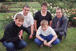 Family group crouching together on grass in park,