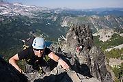 Climber Ian Derrington scrambles the narrow summit ridge of Castle Peak on a traverse of the Tatoosh Range in Mount Rainier National Park, Washington.