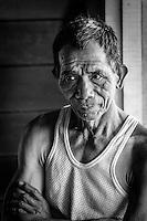 Kelabit man standing by a window in his Bario Longhouse, Sarawak.