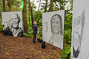 Henham Park, Suffolk, 21 July 2019. The artist in residence works on his pieces in the woods-  watchedf by teh forest pixies, who also act as fire wardens. The 2019 Latitude Festival.