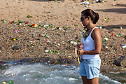 Young Brazilian woman making offerings of flowers to the sea in honour of Yemanja. February 2nd is the feast of Yemanja, a Candomble Umbanda religious celebration, where thousands of adherants visit the Rio Vermehlo Red River to pay their respects to Yemanja, the Orixa goddess of the Sea and water.