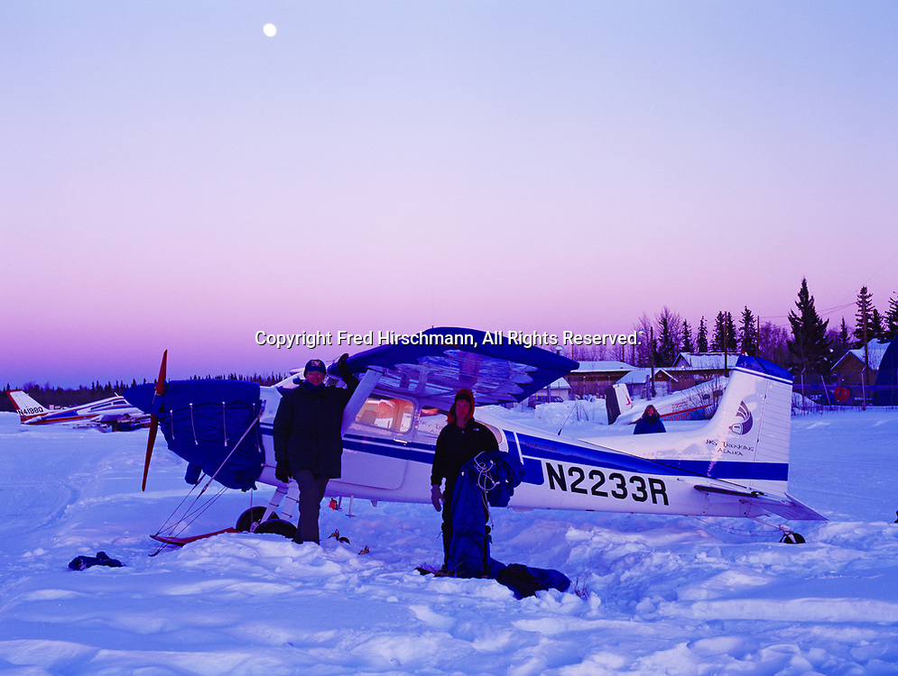 Guest Dave Nelson with pilots Bill Dormer and Lori Egge placing wing covers on Sky Trekking Alaska's Cessna 185s parked for the evening during the Iditarod Sled Dog Race, McGrath, Alaska.