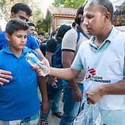 Bashir, a MSF translator gives water to refugees and immigrants that are waiting to be transported from Molyvos to one of the camps in Mytiline.