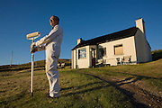 Outdoor decorator stands with roller in evening sunshine near hilltop cottage wall in hamlet of Hallin, Waternish, Skye