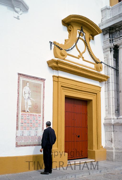 Man looking at bullfight poster in Seville, Spain