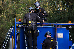 Thames Valley Police officers film the roof of a HGV after removing by force an anti-HS2 activist glued there with a rope around his neck in order to block its passage to works for the HS2 high-speed rail link on 28 September 2020 in Denham, United Kingdom. Environmental activists continue to try to prevent or delay works on the controversial £106bn project for which the construction phase was announced on 4th September from a series of protection camps based along the route of the line between London and Birmingham.