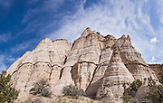 """Cave Loop Trail. See fantastic hoodoos and a great slot canyon in Kasha-Katuwe Tent Rocks National Monument, in New Mexico, USA. Hike the easy Cave Loop Trail plus Slot Canyon Trail side trip (3 miles round trip), 40 miles southwest of Santa Fe, on the Pajarito Plateau. Distinctive cone-shaped caprocks protect soft pumice and tuff beneath. Geologically, the Tent Rocks are made of Peralta Tuff, formed from volcanic ash, pumice, and pyroclastic debris deposited over 1000 feet thick from the Jemez Volcanic Field, 7 million years ago. Kasha-Katuwe means """"white cliffs"""" in the Pueblo language Keresan. This panorama was stitched from 4 overlapping photos."""