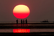 Four people walking the flats pause to watch the sun set. If you look closely, there are some sunspots.