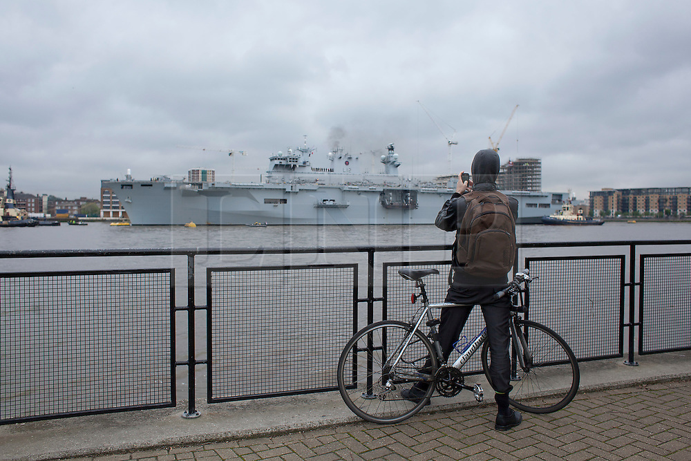 © Licensed to London News Pictures. 04/05/2012. LONDON, UK. A member of the public uses his phone to take a picture of HMS Ocean, the Royal Navy's helicopter carrier, after she made her way up the Thames to moor in Greenwich, London, today (04/05/12). HMS Ocean has been deployed as part of an exercise involving the RAF, British Army and Royal Navy taking place across London as part of security preparations for the 2012 London Olympic Games. Photo credit: Matt Cetti-Roberts/LNP