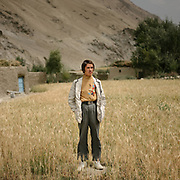A Wakhi teenager returns from school. His name is Iso. Wakhi fashion.  Here he wears his mother;s handmade designer shirt and fake diamond trim on the edge of his coat.The traditional life of the Wakhi people, in the Wakhan corridor, amongst the Pamir mountains.