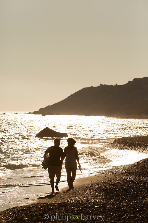 Silhouette of two people walking on sea beach at sunset, Paphos, Cyprus