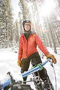 One man riding a fat tire mountain bike through beautiful apen trees on a snowy winter day in Breckenridge, Colorado.