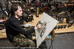 """An artist paints Vlad Romanov""""s Leecoln Hotrods' Shovelhead in the Custom and Tuning Show, the custom bike show portion of the big Motor Spring bike show in Moscow, Russia. Sunday April 23, 2017. Photography ©2017 Michael Lichter."""