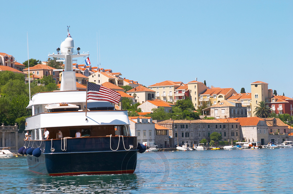 A very big luxurious pleasure motor boat yacht ship, blue and white, American registered with flag, called (name digitally removed), with villas in the background, approaching the dock key. Luka Gruz harbour. Babin Kuk peninsula. Dubrovnik, new city. Dalmatian Coast, Croatia, Europe.