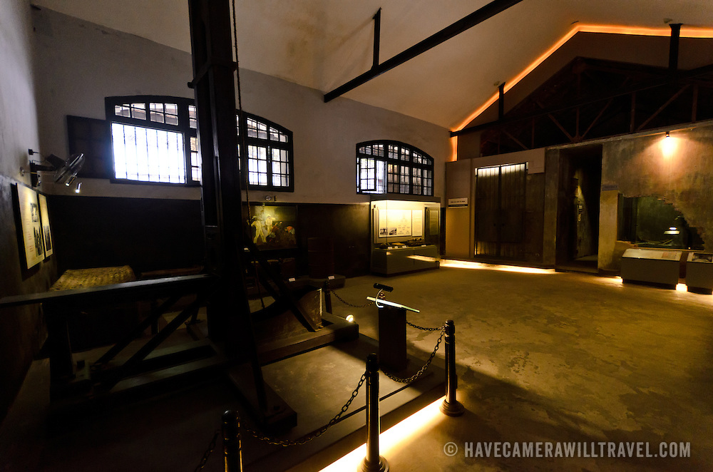 An exhibit room at Hoa Lo Prison. At left is one of the two guillotines the French colonial government used to execute those condemned to death. At right is the entrance to the row of cells for prisoners scheduled for execution. Hoa Lo Prison, also known sarcastically as the Hanoi Hilton during the Vietnam War, was originally a French colonial prison for political prisoners and then a North Vietnamese prison for prisoners of war. It is especially famous for being the jail used for American pilots shot down during the Vietnam War.