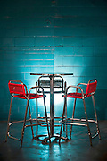Brightly colored orange chairs and table in front of a turquoise wall.