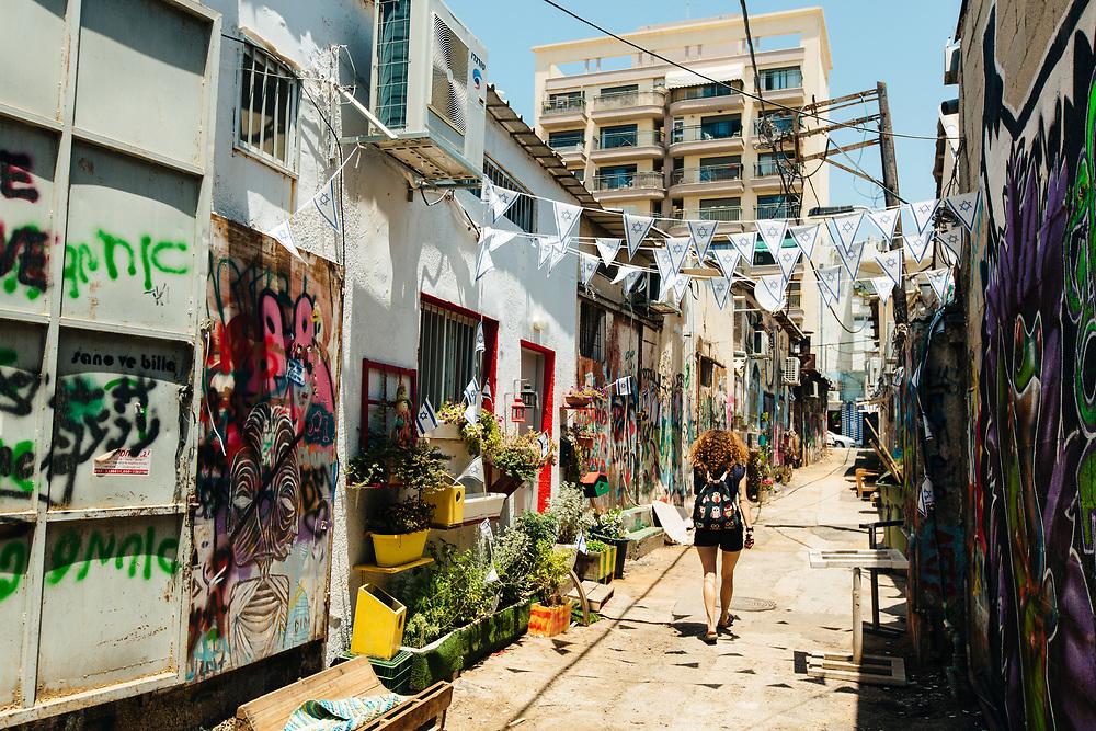 A woman walks past street art and graffiti in Florentin Neighborhood, Tel Aviv, Israel, on July 4, 2018.