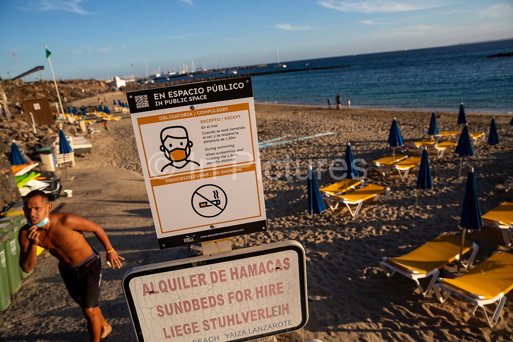 A man walks past a sign showing rules for wearing facemasks on the beach at Playa Dorada in Lanzarote, Spain on 22nd November 2020. Beaches and resorts across the island are nearly deserted since tourism plummeted due to Covid restrictions elsewhere in Europe. Although the Canary Islands have been relatively unscathed by the virus, with 155 lives lost from 2.1 million residents, the region is heavily dependent on tourism and locals are hoping that numbers recover as lockdown measures ease and vaccines potentially reduce the numbers of infections.