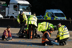 Ockham, UK. 21st September, 2021. Surrey Police officers monitor Insulate Britain climate activists glued onto the clockwise carriageway of the M25 between Junctions 9 and 10 as part of a campaign intended to push the UK government to make significant legislative change to start lowering emissions. Both carriageways were briefly blocked before being cleared by Surrey Police. The activists are demanding that the government immediately promises both to fully fund and ensure the insulation of all social housing in Britain by 2025 and to produce within four months a legally binding national plan to fully fund and ensure the full low-energy and low-carbon whole-house retrofit, with no externalised costs, of all homes in Britain by 2030.